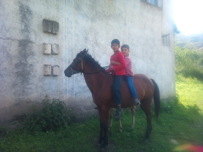 Boys from the village bareback horse-riding